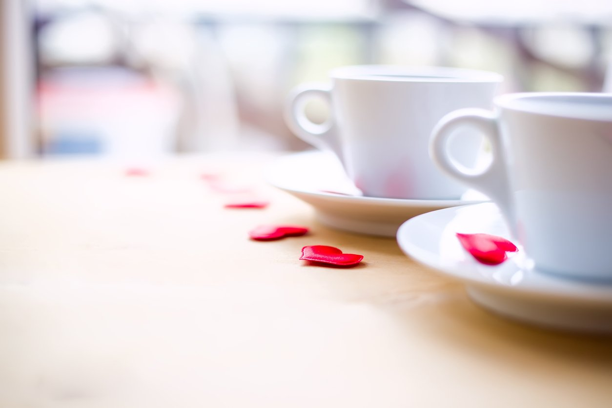 Couple of green tea teacups decorated by red hearts on wooden table.
